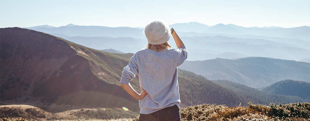 Girl looks out over mountainous landscape